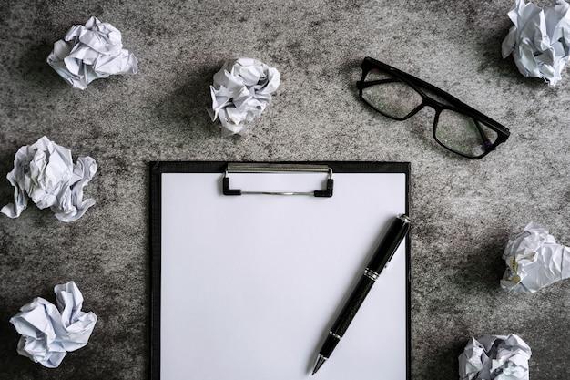 メガネとデスクオフィス、創造性の問題の概念上のファイルフォルダーで紙を丸めてボール