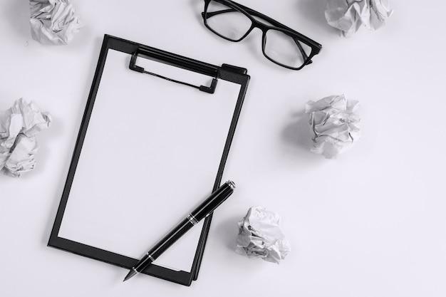 メガネとデスクオフィス、創造性の問題の概念上のファイルフォルダーでしわくちゃの紙のボール