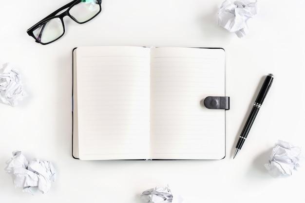メガネとデスクオフィス、創造性の問題の概念上のノートブックのしわくちゃの紙のボール