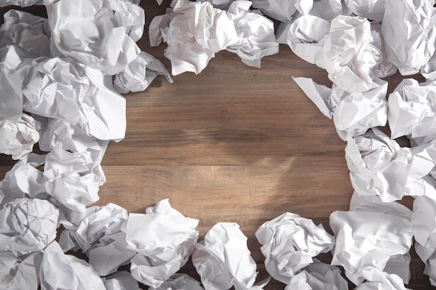 Crumpled paper balls on wooden background.