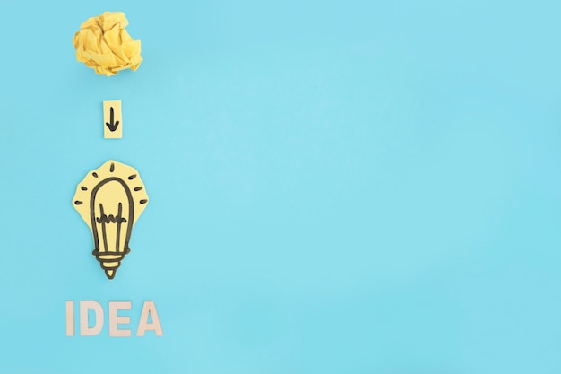 Carta stropicciata sulla freccia in giù sulla lampadina idea di carta