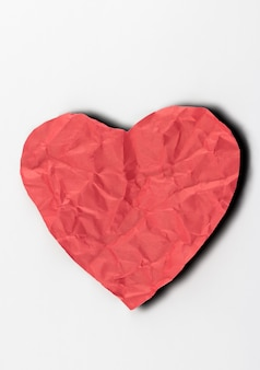 Crumpled paper heart on white background.