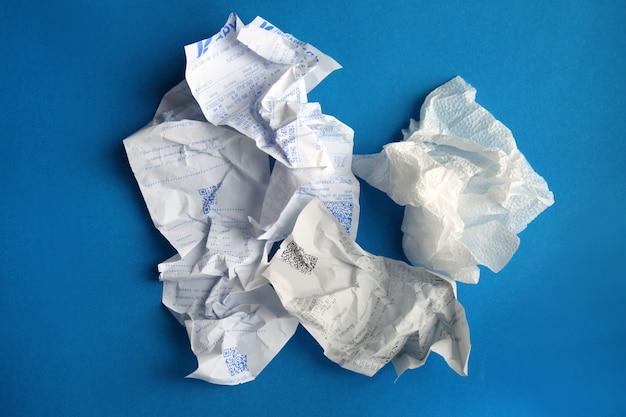 Мятая бумага - это разновидность мусора на простом синем фоне концепция утилизации отходов