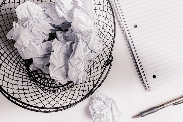Crumpled paper notes in wired basket bin.