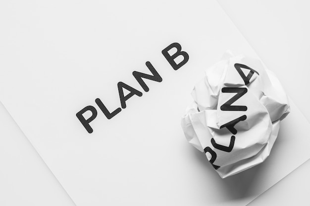 Crumpled paper plan a and clean sheet paper plan b on white background.