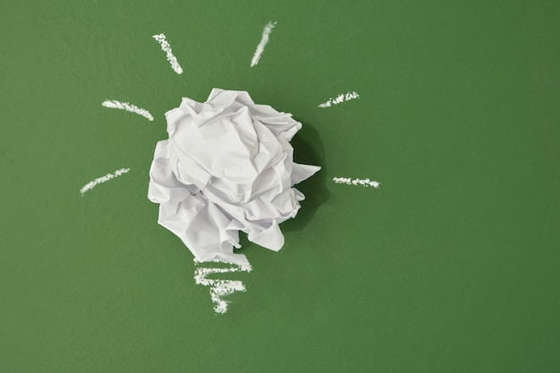 Crumpled paper in the shape of a light bulb on a green chalk board background, planet pollution concept