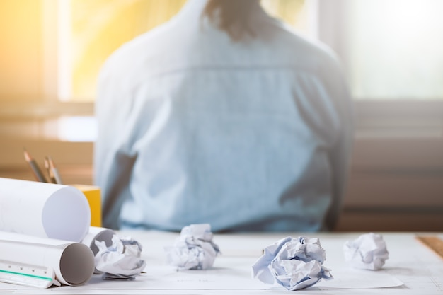 Crumpled paper on table with unhappy businesswoman was frustrated