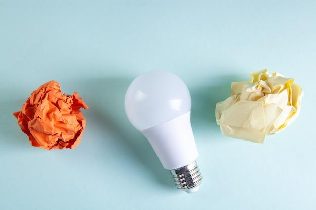 Мятые бумаги и лампочка на столе
