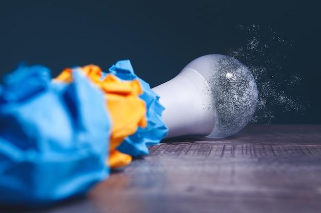 Мятые бумаги и исчезающая лампочка на столе