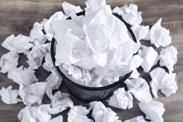 Мятые бумаги в мусорном баке.