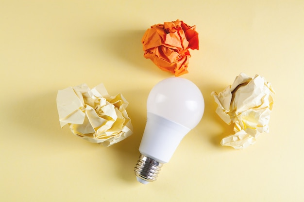 Crumpled papers and a light bulb on the table