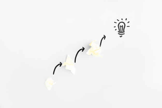 Crumpled papers with directional arrows pointing toward light bulb on white background