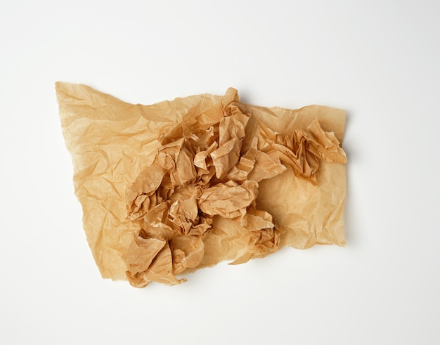 Crumpled piece of brown paper sheet on white