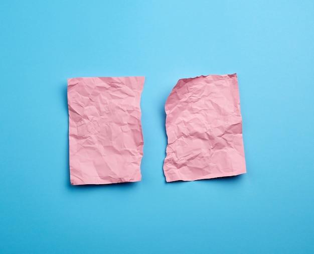 Мятый розовый лист бумаги, разорванный на две части на синем