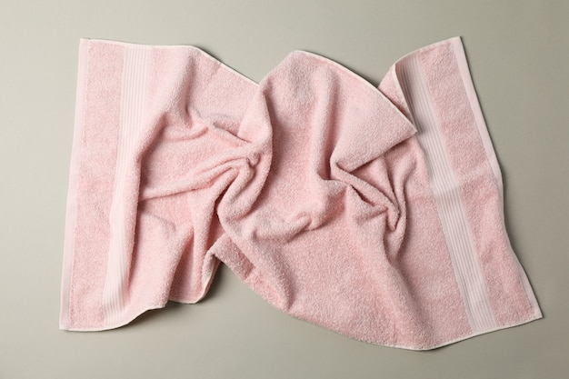 Crumpled pink towel on grey, top view