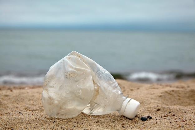 海を背景に砂浜のしわくちゃのペットボトルデイリサイクル