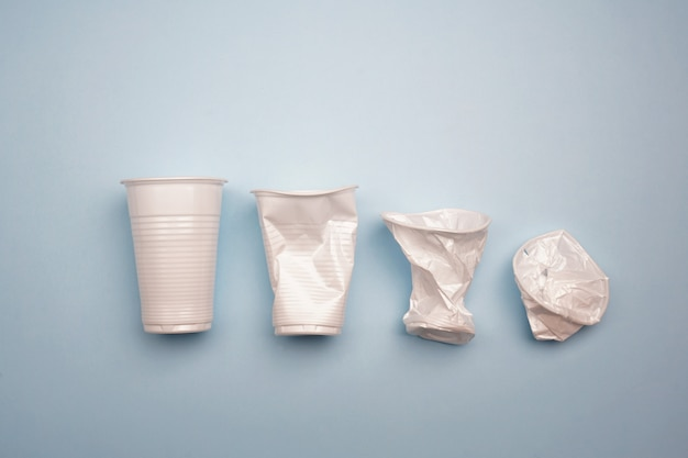Crumpled plastic cups on bright blue background. creative minimal concept
