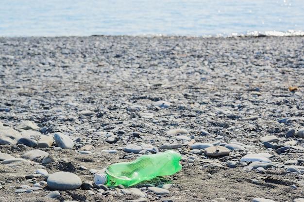 小石のビーチでしわくちゃのプラスチック製の緑のボトル、環境保護の概念、水平ライフスタイルストックフォト画像の背景