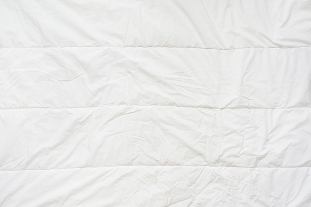 Crumpled quilt white blanket texture. close up. top view
