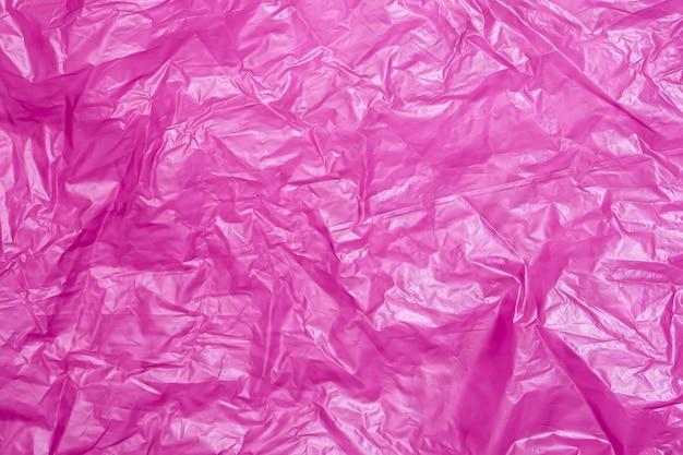 しわくちゃの赤いライラックのビニール袋の抽象的なテクスチャの背景の表面。