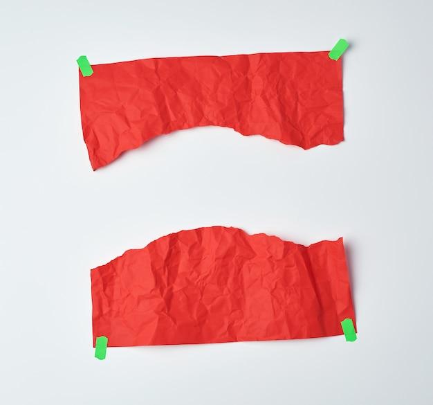 Мятый красный лист бумаги, разорванный пополам и приклеенный зеленой липкой лентой
