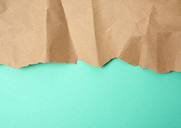 Мятый лист коричневой оберточной бумаги на зеленом фоне, фон для дизайнера