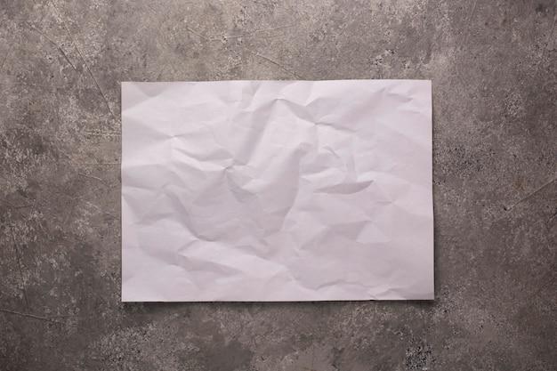 콘크리트 벽에 구겨진 종이 시트.