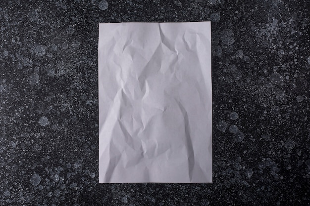 A crumpled sheet of paper is glued to the wall
