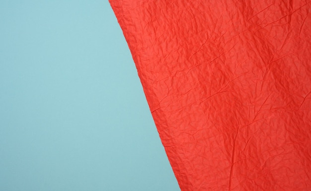Crumpled sheet of red paper on a blue background, creases and scuffs. place for inscription, full frame