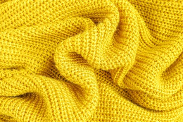Crumpled soft knitted fabric of yellow fluffy woolen yarn closeup, beautiful cozy