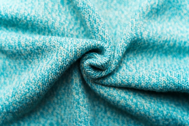 Crumpled texture of a blue turquoise knitted fabric. sweater background