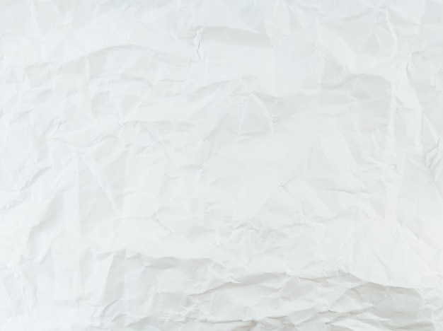 Crumpled textured white paper sheet with empty space.
