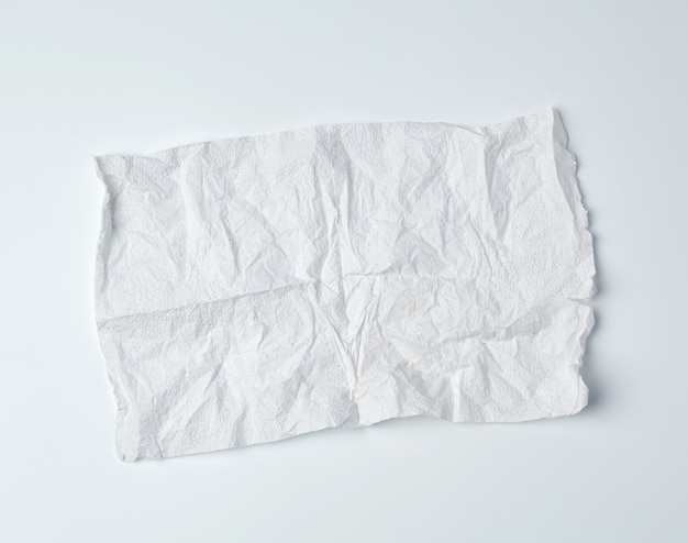 Crumpled torn soft white sheet of paper towel with curled corners