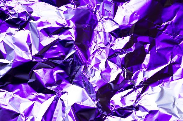 しわくちゃの鮮やかな紫のアルミホイルの背景