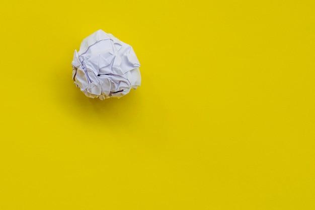 黄色の背景にしわくちゃの白い紙のボール