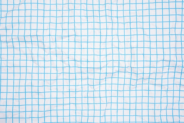 Crumpled white paper texture in a cage, blue lines, school notebook