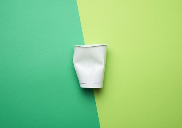 Мятый белый пластиковый стакан на зеленом фоне, плоская планировка