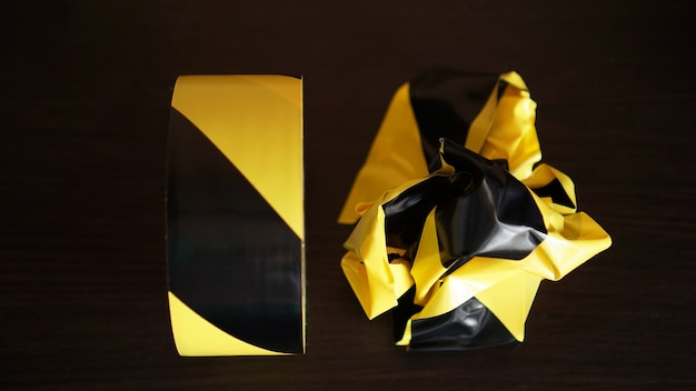 Crumpled yellow and black tapes on dark background