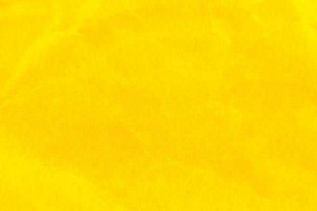 しわくちゃの黄色い紙の背景。リアルなマクロのボロボロのテクスチャー。写真を閉じます。