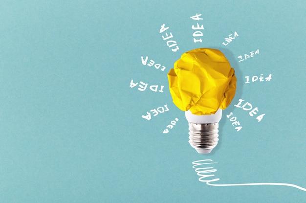 青い背景の周りに碑文のアイデアを持つしわくちゃの黄色い紙の電球