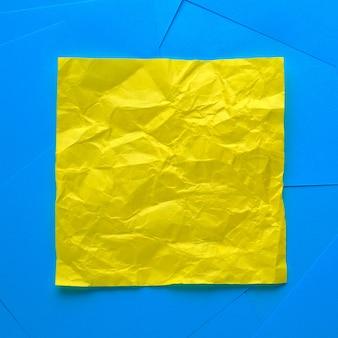 情報リマインダーのしわくちゃの黄色の粘着ステッカー。テキストのためのスペース。その隣には空の青いステッカーがあります。