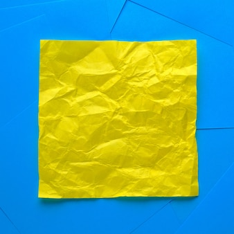 Crumpled yellow sticky sticker for information reminder. space for text. next to it are empty blue stickers.