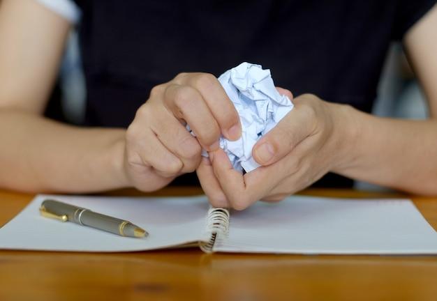 Crumpling the sheet of paperwork.