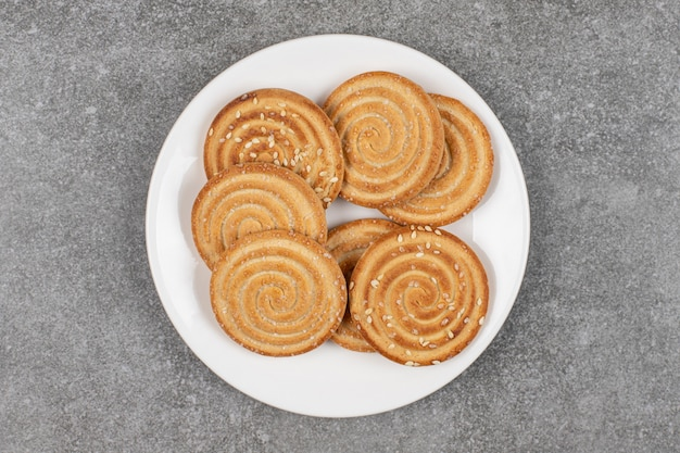 Biscotti croccanti ai semi su piatto bianco.