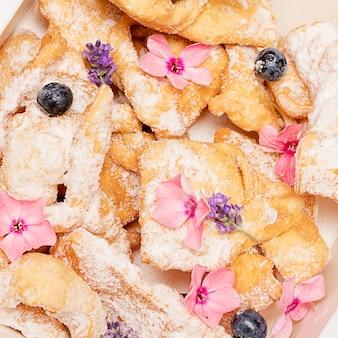 花で飾られた粉砂糖をまぶしたカリカリのもろい細いストローの小枝クッキー。自家製ベーキング。ベーカリーと美的で美しい料理の概念。甘い人生。クローズアップ写真