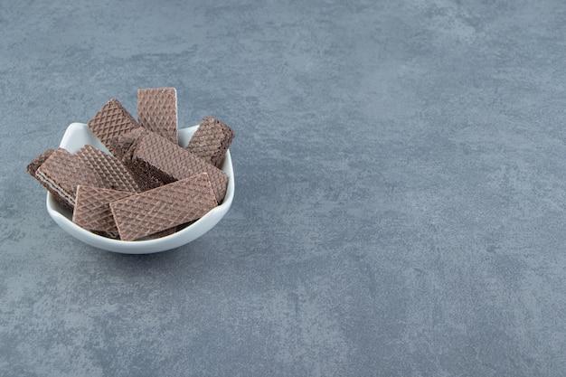 Cialde croccanti al cioccolato in ciotola bianca.