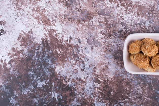 Хрустящее печенье в белом керамическом блюдце с правой стороны.