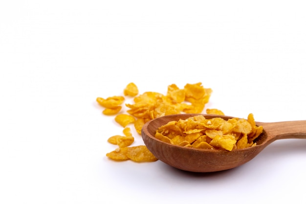 Crunchy corn flakes, cereal, muesli pile in wooden spoon on white