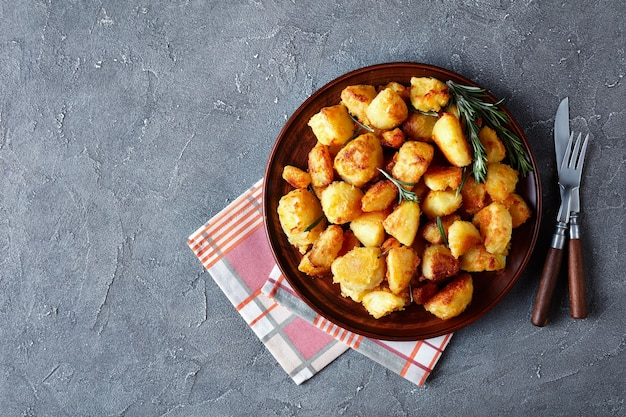 Crunchy cornmeal breaded roast potatoes with spices and rosemary served on a clay dish