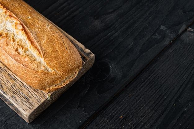 カリカリのフランスパン、テキスト用のコピースペースのある黒い木製のテーブル